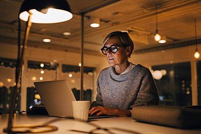 Confident mature female business professional using laptop while sitting at desk working late in office - p426m2194899 by Maskot