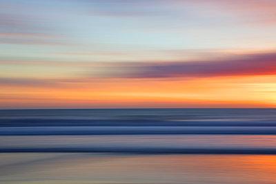 Defocused view of ocean waves on beach under sunset sky - p555m1411726 by Sam Diephuis