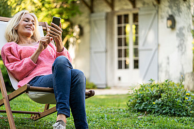 Smiling mature woman using smartphone while sitting on deckchair - p623m2271827 by Frederic Cirou