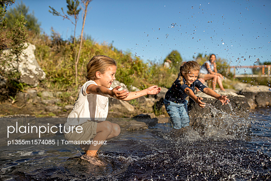 Children playing on lake - p1355m1574085 by Tomasrodriguez
