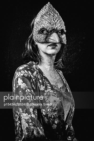 Woman wearing a bird mask - p1543m2262412 by Sophia Snadli