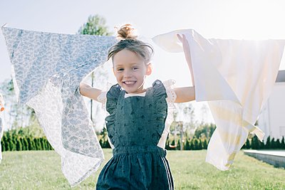 portrait of a young girl playfully running through washing at home - p1166m2201726 by Cavan Images