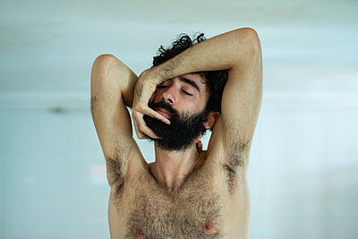 Strange pose of bare-chested young man - p1567m2173040 by Claire Picheyre