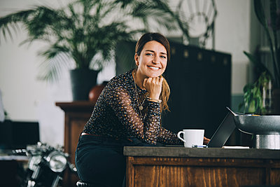 Portrait of smiling businesswoman with hand on chin sitting at kitchen island in creative office - p426m2127472 by Maskot