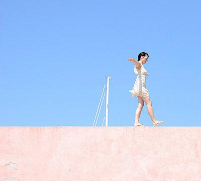 Woman balancing on wall - p42917627f by JLPH