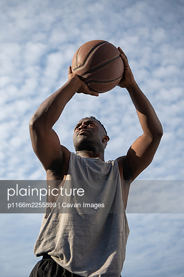 Strong black basketball player throwing ball - p1166m2255899 by Cavan Images