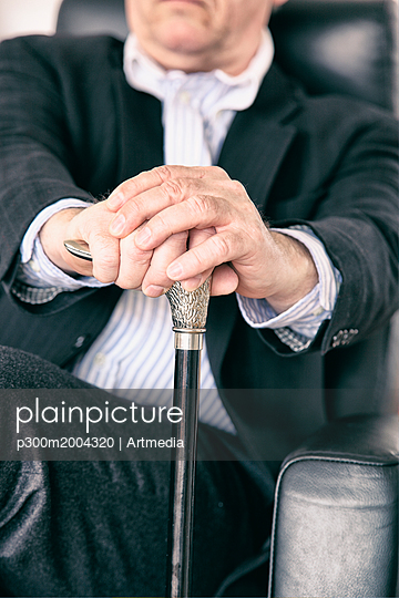 Hands of senior sitting on black leather chair holding silver handle of walking stick, close-up - p300m2004320 von Artmedia