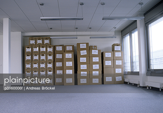 empty office space with neatly stacked moving boxes in background