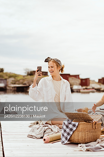 Smiling woman taking selfie sitting on jetty against sky during picnic - p426m2238130 by Maskot