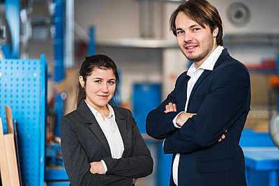 Confident business people smiling while standing with arms crossed at industry - p300m2250726 by Daniel Ingold