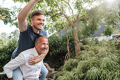 Father giving piggyback ride to cheerful son in backyard - p300m2275060 by Gustafsson