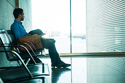 Young businessman at waiting area looking out of window - p300m997934f by Uwe Umstätter
