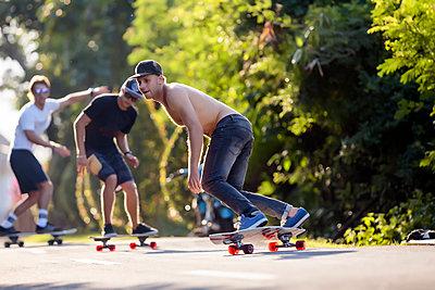 Young men skateboarding in street, Canggu, Bali, Indonesia - p343m1543790 by Konstantin Trubavin