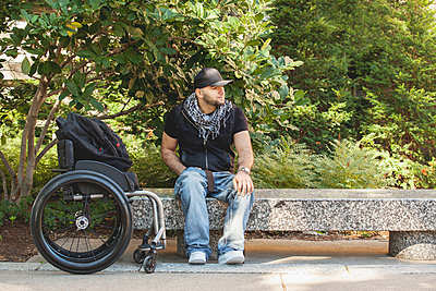 Disabled man and wheelchair sitting on stone bench - p555m1410899 by PhotoAbility
