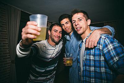 Smiling men drinking in nightclub - p555m1412851 by Inuk Studio