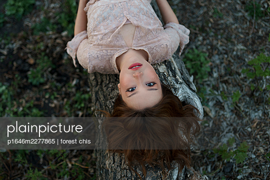 Young woman on a tree trunk - p1646m2277865 by Slava Chistyakov