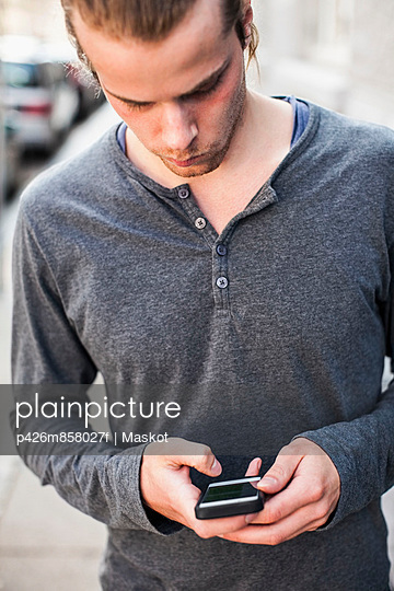 Young man using mobile phone outdoors - p426m858027f by Maskot