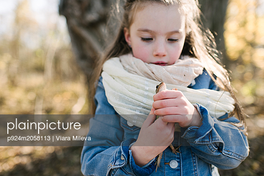 Little girl holding frog in forest - p924m2058113 by Viara Mileva