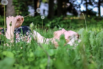 Blonde Frau liegt im Gras - p1019m1425482 von Stephen Carroll