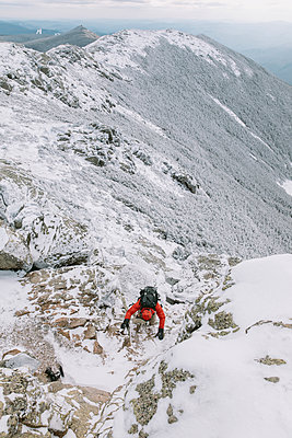 High angle view of backpacker climbing on snowcapped mountain during winter - p1166m2001276 by Cavan Images