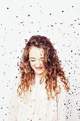 portrait of a young girl with flower petals - p1540m2211022 by Marie Tercafs