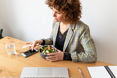 Female freelancer using smart phone while having food at home - p300m2282275 by Sus Pons