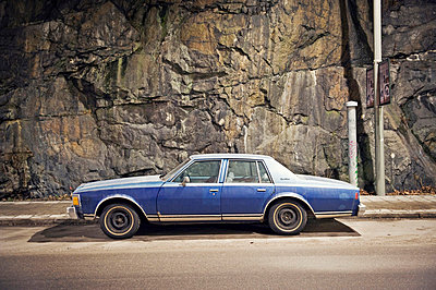 A blue car against a stone wall, Sweden. - p31224532f by Alexander Crispin