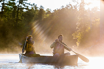A Young Couple Paddles A Canoe Through Morning Mist On Long Pond In Maine's North Woods - p343m1204027 by Jerry Monkman