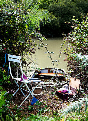 Rowing boat moored on riverbank with folding chair;  bunting and wool Isle of Wight;  UK - p349m920046 by Rachel Whiting