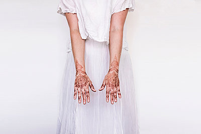 Woman in white dress with henna tattoo on hands - p429m2075431 by Tom Dunkley