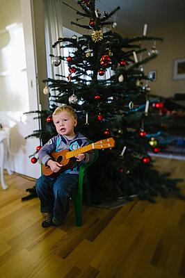Kleiner Junge mit Spielzeuggitarre am Weihnachtsbaum - p819m1065052 von Kniel Mess