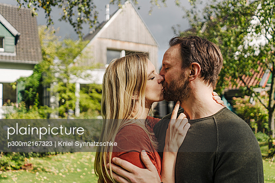 Happy couple kissing in garden, in front of their dream house - p300m2167323 by Kniel Synnatzschke