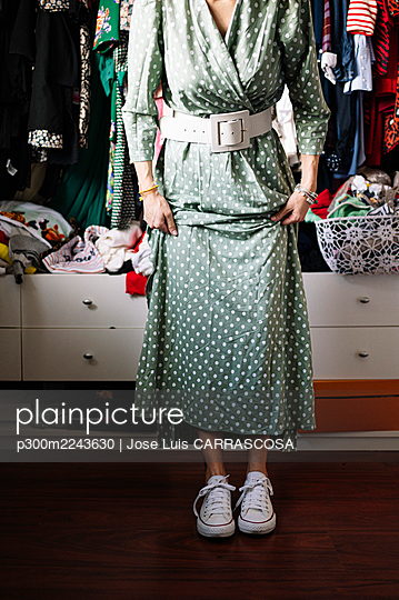 Woman in spotted green dress wearing white shoes against clothes hanging in rack at apartment - p300m2243630 by Jose Luis CARRASCOSA
