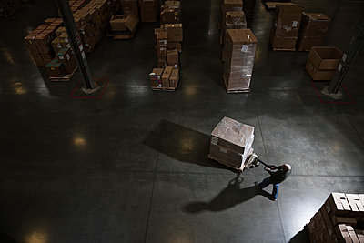 Warehouse worker using a manual pallet jack to move some products in a distribution warehouse. - p1100m2002283 by Mint Images