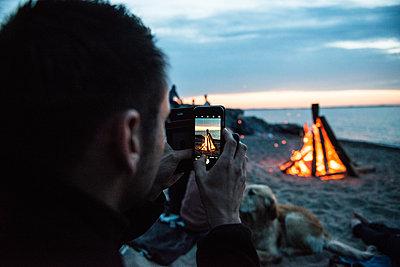 Mann fotografiert Lagerfeuer am Strand - p1142m1362697 von Runar Lind