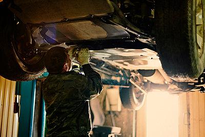Rear view of mechanic repairing vehicle in workshop - p1166m1489347 by Cavan Images