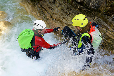 High angle view of friends canyoneering amidst waterfall - p1166m2113027 by Cavan Images
