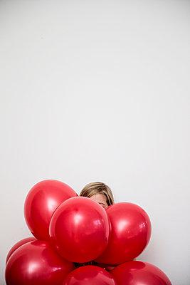 Mädchen versteckt hinter roten Ballons - p1212m1091998 von harry + lidy