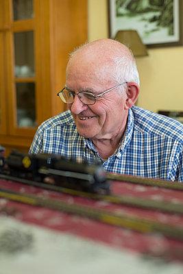 Smiling senior man with his model railway - p300m1023184f by Ramon Espelt