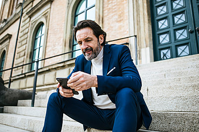 Portrait of bearded mature businessman sitting on stairs looking at cell phone - p300m2140502 by Johanna Lohr