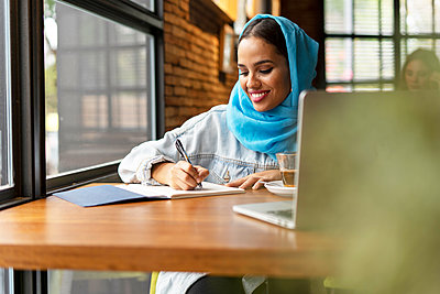 Businesswoman wearing turquoise hijab in a cafe and writing in notebook - p300m2143607 by Eloisa Ramos