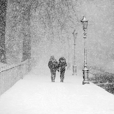Couple walking together in snow-covered park during heavy snowfall - p300m2281390 by Alex Holland