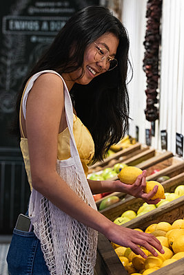Barcelona, Spain. Asian woman in grocery store. Asian ethnicity, healthy eating, Km 0, small business, vegetable, shopping bag, food, sustainability, shopping, ecological, fruit, customer, healthy, buying, positive, payment, health awareness, market - p300m2282776 von NOVELLIMAGE