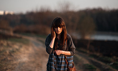 Caucasian woman standing on dirt road - p555m1305568 by Marat Safin