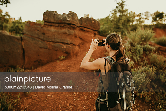 Female trekker taking picture on smart phone while standing in forest - p300m2213948 by David Molina Grande