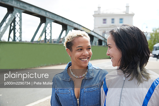 Lesbian couple smiling while looking at each other on bridge - p300m2290734 by Pete Muller