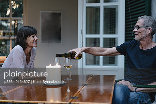 Happy married couple has a glass of wine in the evening - p586m2134827 by Kniel Synnatzschke