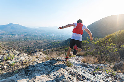 Backside of a male trail runner running down rocky terrain as the sun sets  over the mountains of El Arenal, Hidalgo, Mexico. - p1166m2124195 by Cavan Images