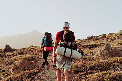 Two men walk on trail with camping gear and Mount Teide in background - p1166m2129947 by Cavan Images