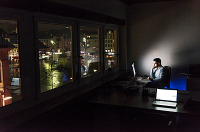 Businessman working on computer in office at night - p300m1580743 by Uwe Umstätter